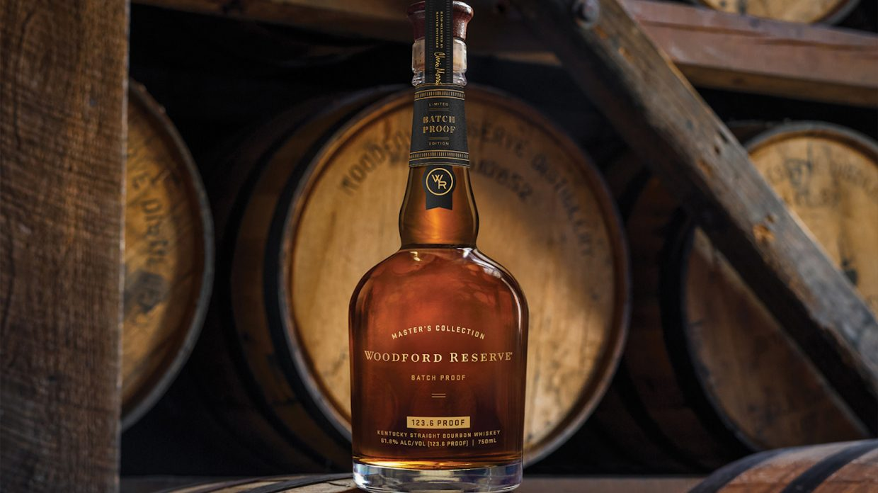 A bottle of Woodford Reserve Batch Proof (2020 Edition) sits on top of a whisky barrel, with several barrels visible behind it.