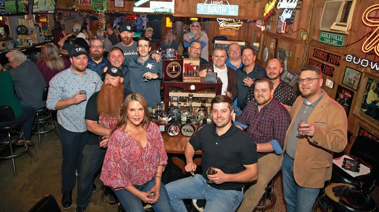 East Texas Bourbon Society members, including Longview chapter president Cole Tomberlain, clad in a black polo shirt, sit and stand, holding snifters containing what appears to be whisky, around a table topped with various bottles of whisky, at an unidentified bar at an unidentified location in Texas, on an unspecified date.