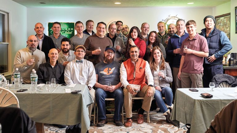 Members of Norfolk Whisky Group gathered at the Norfolk, Massachusetts home of co-founder Bikram Singh, seated in the front row, wearing an orange vest, to taste more than a dozen whiskies.