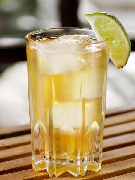 Collins glass filled with whiskey and ginger ale and garnished with a lime wedge