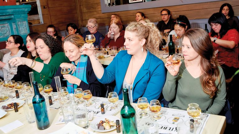 Members of Women Who Whiskey's New York City chapter sit at a long table with Irish whiskey flights in front of them, as well as glass beakers, as they raise whiskey-filled snifters, study the liquid, nose, and taste at cocktail bar Tara Rose on Dec. 16, 2019.
