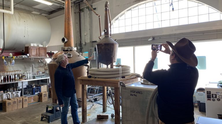A man films another man on a cell phone inside a distillery.