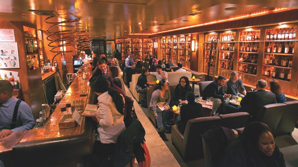 A bunch of people gather at the bar and in booths of the Brandy Library.