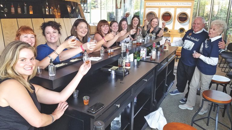 A large group of people are toasting around a bar.