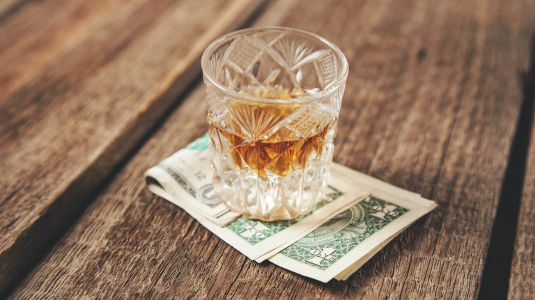 A glass of brown liquid sits on top of a stack of dollar bills.