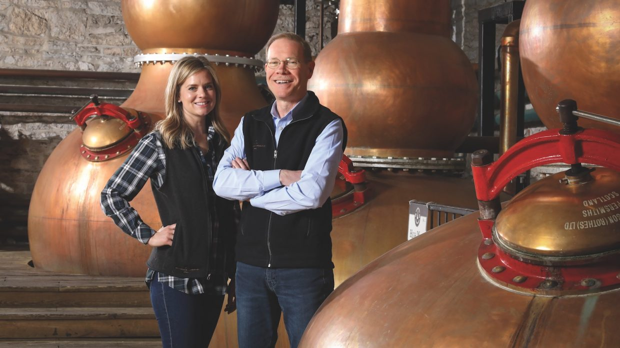 A man and woman stand in front a series of stills in a stillhouse.