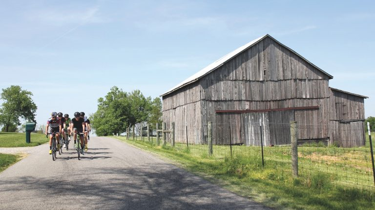 A group of six cyclists rides past a warehouse on a bright, sunny day.