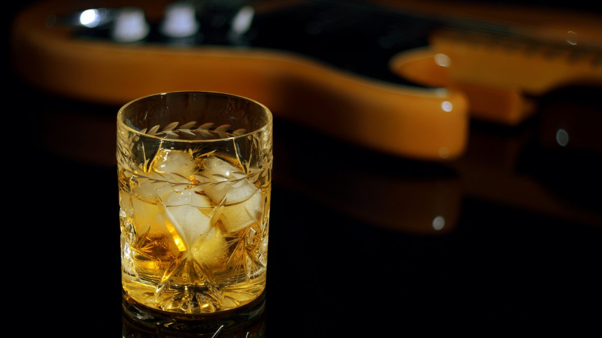 A glass of whiskey on the rocks and old guitar.