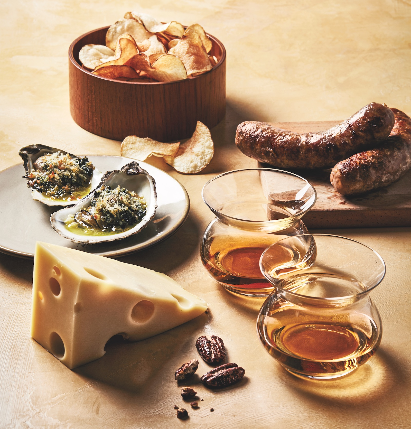 chips, oysters, cheese, sausage, and nuts with two glasses of bourbon