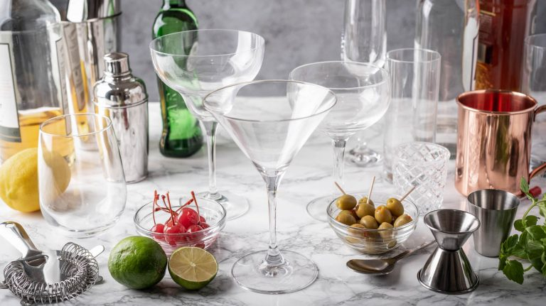 Various cocktail glasses sit center, surrounded by other cocktail materials.