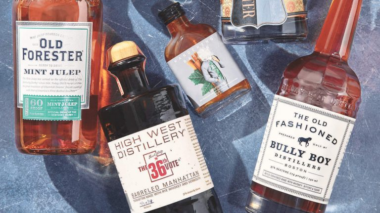 Several ready-to-drink bottled whiskey cocktails—including an Old Forester mint julep, a High West barreled Manhattan, a smoky variation on an old-fashioned from Brooklyn-based bottled cocktail company Wandering Barman, and another old-fashioned from Boston's Bully Boy Distillers—rest on a blue surface.