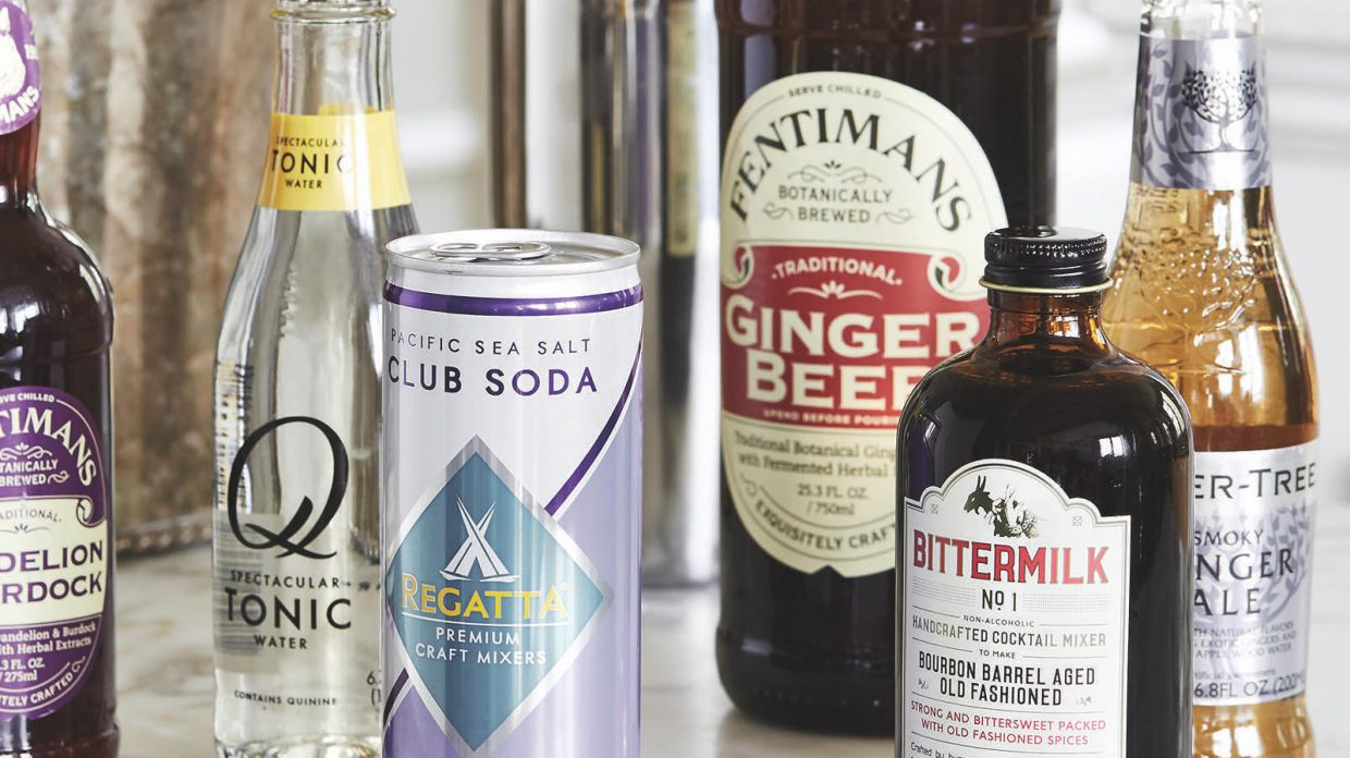 Bottled and canned sodas and cocktail ingredients—including tonic water, club soda, ginger beer, ginger ale, and a cocktail mixer to make an old fashioned—rest on what appears to be a marble surface.