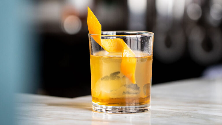 whiskey cocktail in a rocks glass with an orange twist