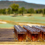 shots of whiskey lined up on a wooden table in front of a golf course