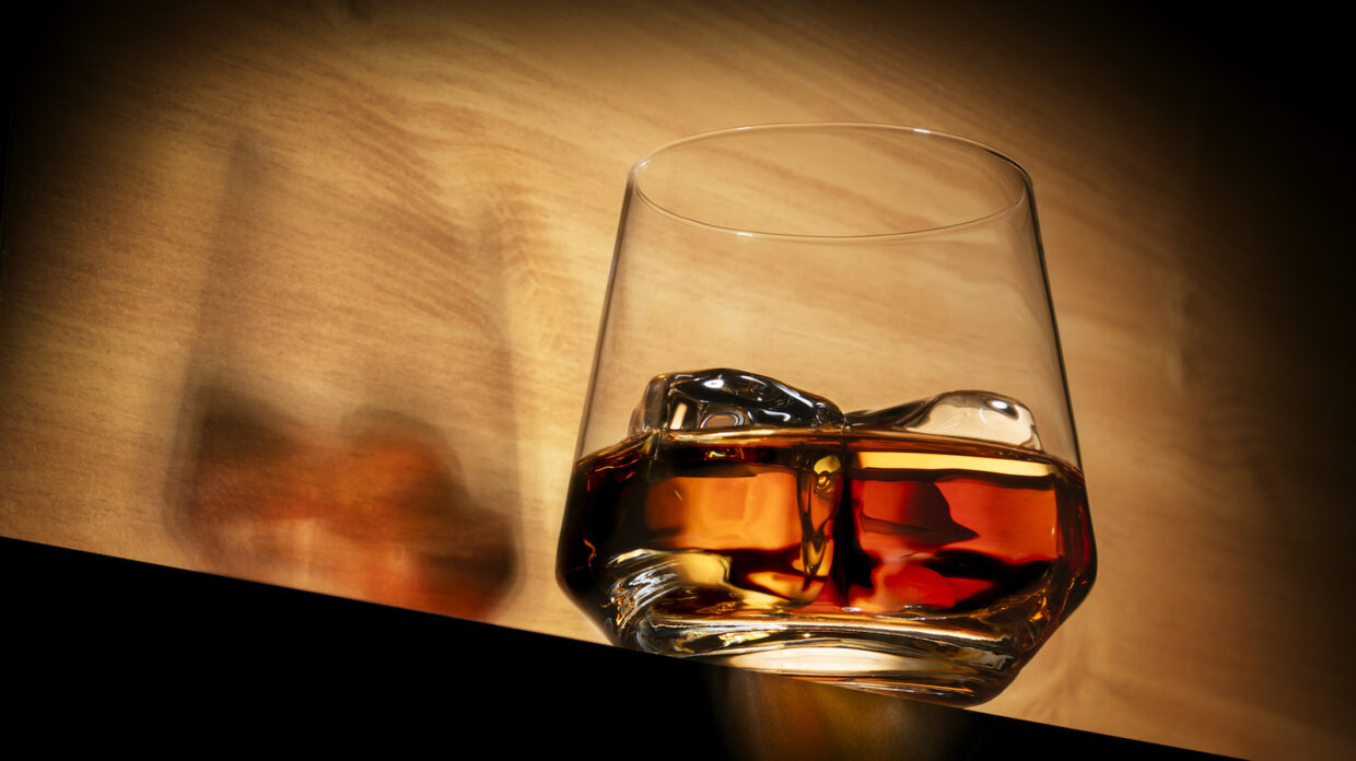 An elegant rocks glass containing what appears to be whisky and two large ice cubes rests on what looks like a dark surface that is cast in shadow, in front of a light-brown background, with light reflecting off the base of the glass.