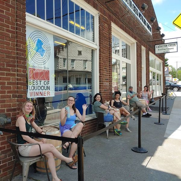 People sit at barrels functioning as sidewalk tables spaced at least 6 feet apart at Catoctin Creek Distilling Co. in Purcellville, Virginia.