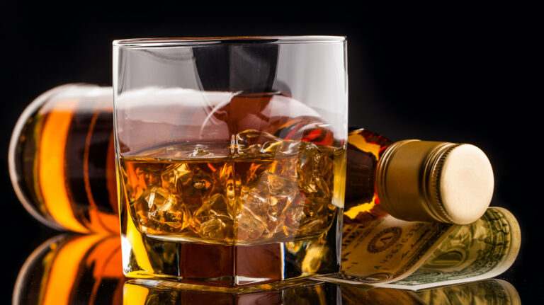 glass of whisky with bottle on reflective surface with black background and dollar money