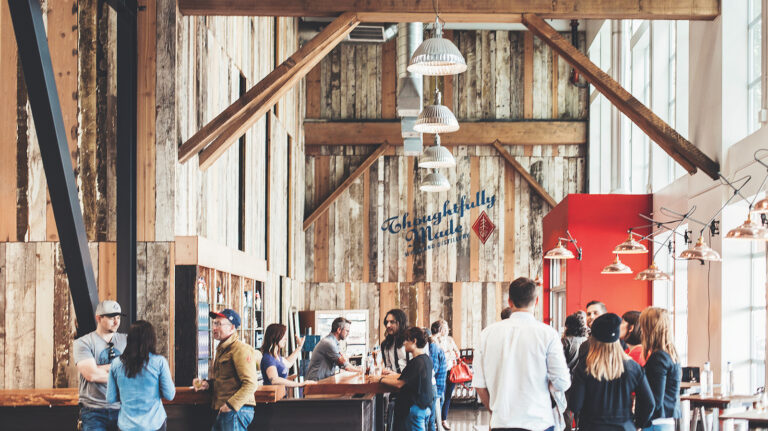People stand around talking and enjoying whiskey at the Cantilever Room at Westland Distillery in Seattle, Washington, a brightly lit space featuring exposed wooden beams overhead.