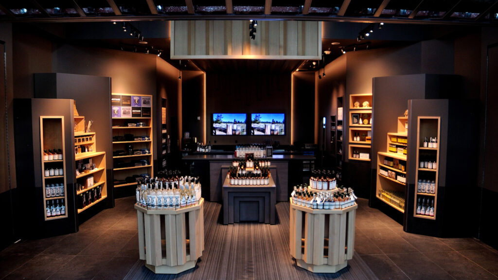A view of Oregon-based Westward Whiskey's tasting room at Portland International Airport with bottles of whiskey atop wooden stands, tables, and on shelves, and Westward T-shirts on shelves too.