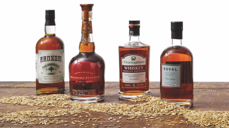 Four bottles of oat whiskey—Ransom the Emerald 1865, Woodford Reserve Master's Collection Oat Grain Bourbon, Dry Fly O'Danaghers 5 year old American Hibernian Single Barrel, and Koval Single Barrel Four Grain—rest on a wooden surface with oats scattered in front of them.