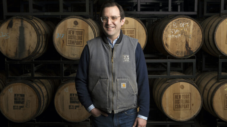 Allen Katz stands in front of several whiskey barrels.