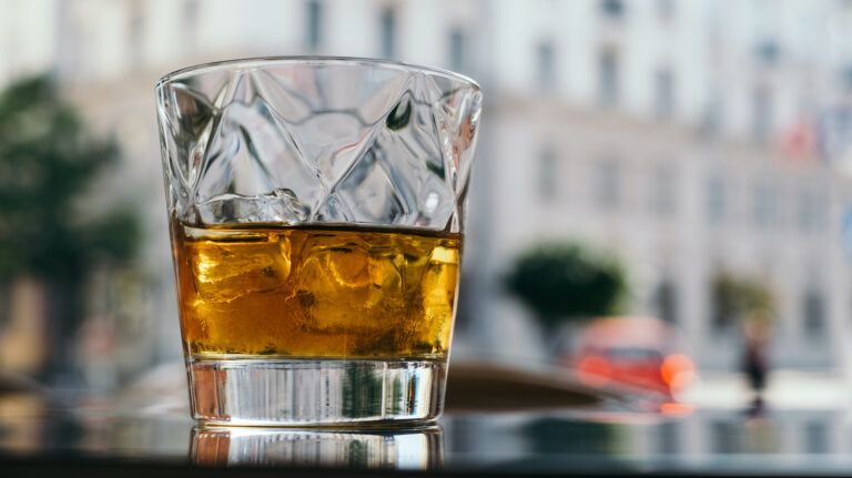 Glass of whisky on a table outdoors