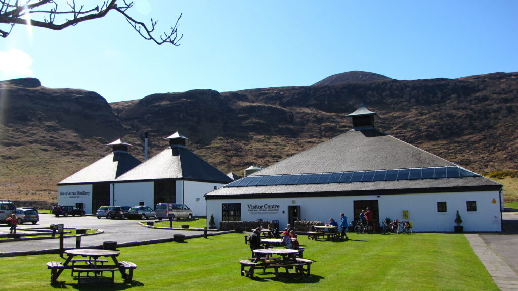 A view of the Arran single malt whisky distillery's visitor center in the village of Lochranza on Scotland's Isle of Arran; visitors sit around picnic tables on a green lawn in the sunshine, next to the visitor center, with mountains and blue skies in the background.