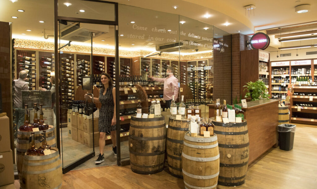 An interior view of Astor Wines & Spirits in New York City, with bottles resting atop barrels.