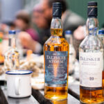 Two bottles of Talisker scotch rest atop a table around which people sit eating oysters and drinking whisky.