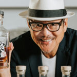 A portrait of the Japanese chef Masaharu Morimoto, wearing a light-colored brimmed hat, dark rimmed glasses, grinning, and holding up a bottle of the whiskey he created in partnership with Rogue Ales & Spirits, which was released in 2020.