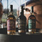 A trio of whiskeys from The Whistler Irish whiskey atop a cask