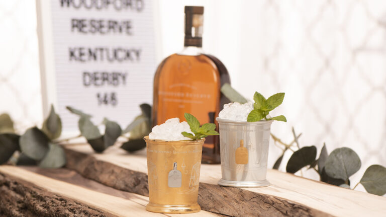 A couple of 2020 Woodford Reserve $1,000 mint julep cups—one gold- ($2,500) and one silver-plated, each packed with crushed ice and garnished with a mint sprig—rest on a slab of wood, with a bottle of Woodford Reserve bourbon in the background, along with a sign advertising the 146th Kentucky Derby.