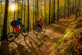couple on biking trail in autumn forest.