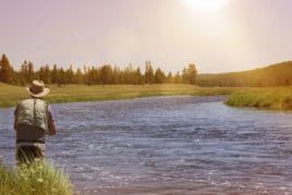 man fly fishing on wide river on sunny day