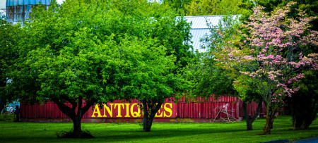 """A large red barn with """"Antiques"""" displayed in large yellow letters behind lush green trees"""