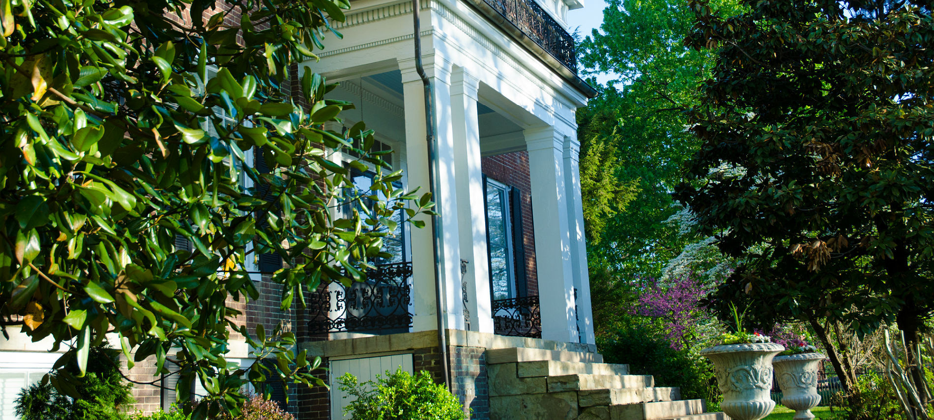Bourbon Manor B&B's portico entrance with white columns and stone staircase flanked by two large urn planters