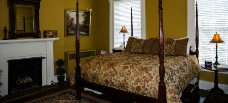 Guestroom featuring mustard walls, white trim, vaulted ceiling and king-size poster-bed with floral bedding