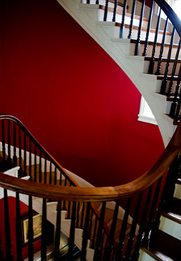 White serpentine staircase with wooden spindled banister, wooden treads, scarlet walls and a bright window