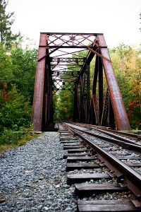Railroad tours crossing bridge in the woods of northern New Hampshire.