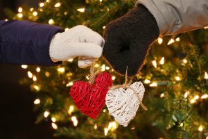 Romantic winter, hands in mittens holding hearts