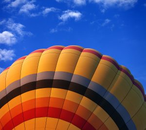 Hot Air Balloon flying against a blue sky and plane fair