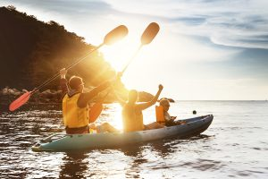family kayaking at sunset