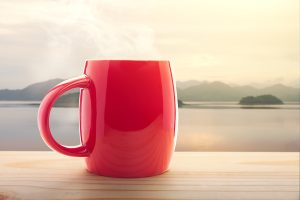 Red coffee cup on porch with water view.
