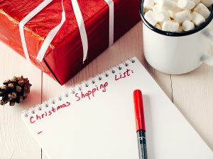 holiday shopping list next to gift and hot chocolate