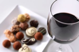 Glass of red wine and delicious chocolate candies