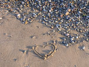 romantic Heart Drawn In Sand On Beach With Pebbles