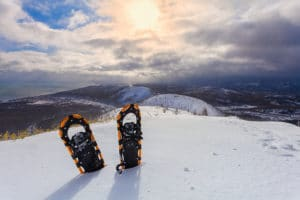 snowshoes in the snow on the winter mountains and sky with clouds background.
