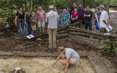 Crew Chief Joe Downer explains the goals of the Slave Cemetery Survey to the public while Leah Stricker uncovers a burial.