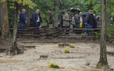 Visitors look on at a row of grave shafts uncovered during the Slave Cemetery Survey.
