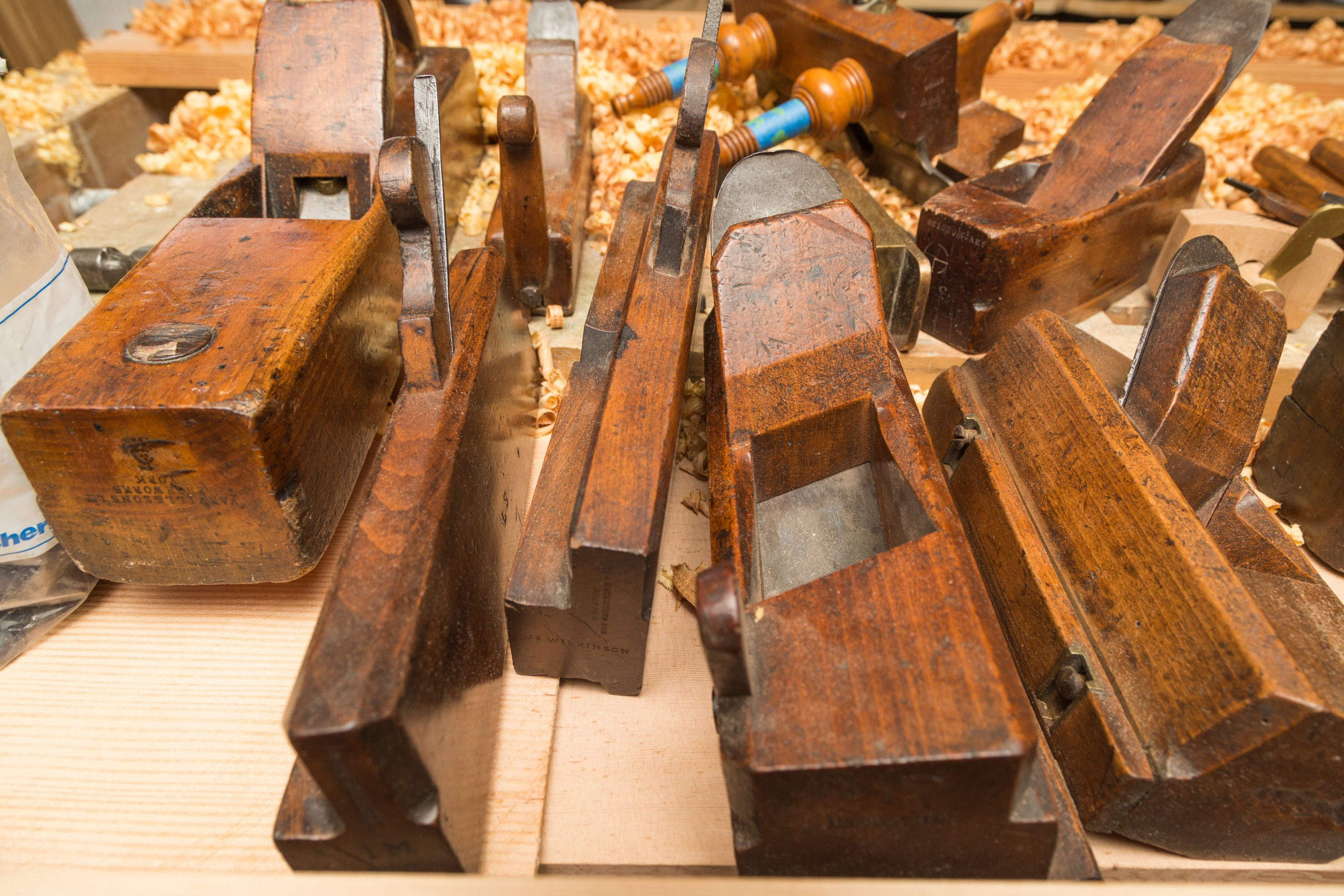 Planes shape wood by using strength to force the iron blade across the surface. From left: badger plane, two molding planes, and two dado planes.